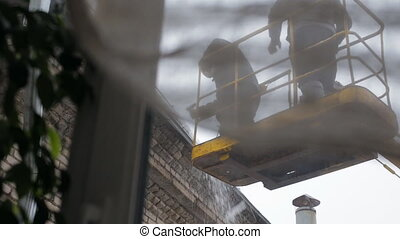 Workers in skylift removing icicles from roof - view from...