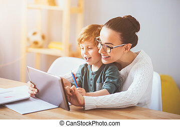 Delighted mother teaching her son using a tablet