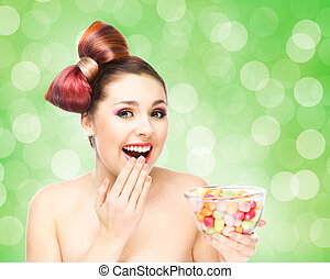 Beautiful smiling girl eating sweets from a bowl on bubble...