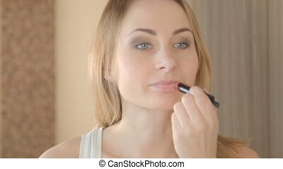 Beautiful attractive young women puts makeup on in the...