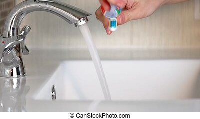 A woman brushes and cleans her teeth in the bathroom.