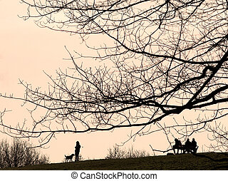 Silhouette of dog walkers on Hampstead Heath London with...