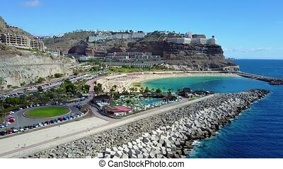 Camera fly over the crowded Amadores beach at Gran Canaria -...