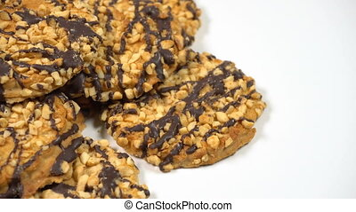Cookies with nuts and chocolate rotates on a white table