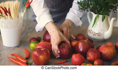 Woman chef putting fresh fruits and vegetables on wooden...