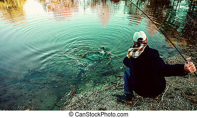 Fisherman with fishing rod and landing net during pulling...
