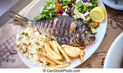 Bream with potato, rice and salad, mediterranean food