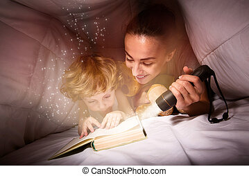 Pretty woman and her son reading a book at night
