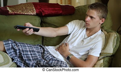 Teenager Channel Surfing - Teenage boy uses a remote to...