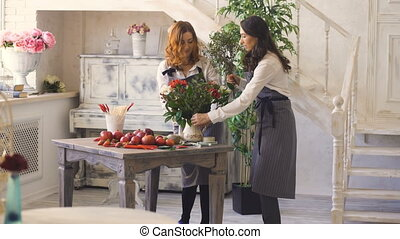 Two chef woman and florist preparing flowers, fruits and vegetables for making fruit bouquet