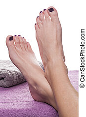 Bare feet with pedicure propped by towel on soft purple...
