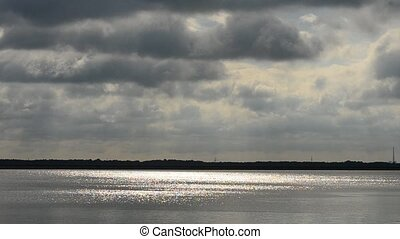 Dramatic grey clouds over water - Dramatic grey clouds over...