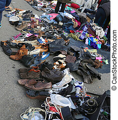used clothes and shabby clothing in an outdoor flea market -...