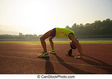 young asian woman backbending on stadium track