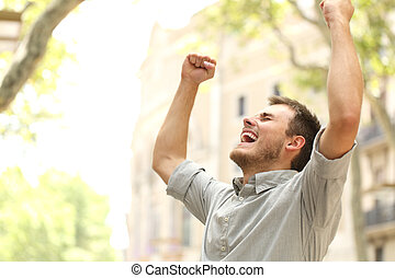 Excited man raising arms in the street - Portrait of an...