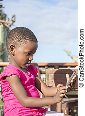 Little Girl Looks at Mobile Phone Screen.