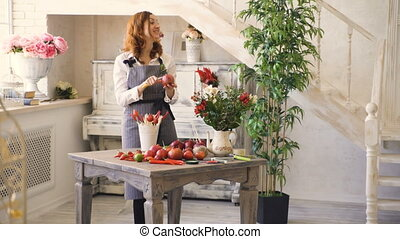 Chef woman and florist preparing fruits and vegetables for making fruit bouquet and talks smiling