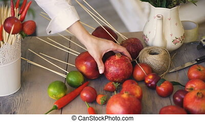 Woman chef takes pomegranate from wooden table with fruits and vegetables preparing before cooking