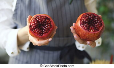chef woman cook in apron shows pomegranate closeup in the...