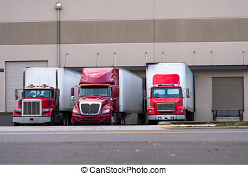 Three red semi trucks are among the dock for loading trailers