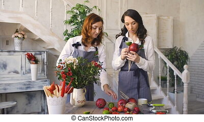 Two young handsome chef florists work at flowers fruit shop making fruit and vegetable bouquet
