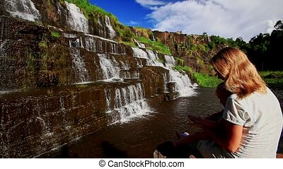 Mother Sits Holds on Knees Little Girl Shows Waterfall...