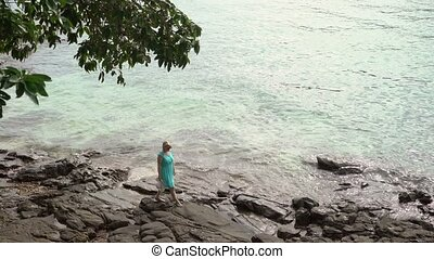 Young woman walking on the rocky beach - Young woman in blue...