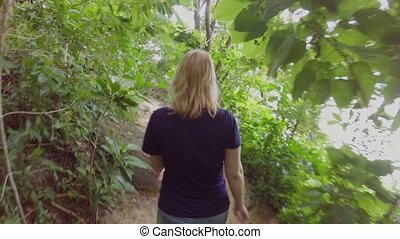 Woman hiking in path in jungle - Blonde woman hiking in path...