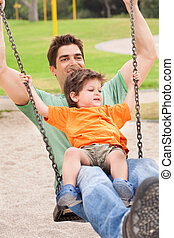 Father enjoying swing ride with his son in the park,...