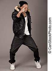 Street dancer showing his dance skills on grey background
