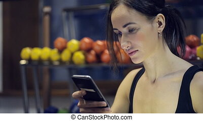 Woman sitting inside gym, looking in phone, relaxing. Fit...