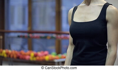 Close up chest of woman shakes biceps with dumbbells in...