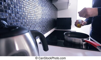 In the kitchen man pours oil onto the hot pan on an...