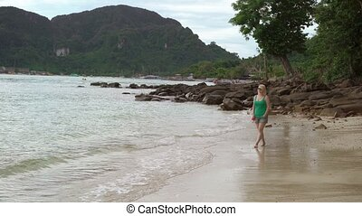 Woman walking alone on wild beach
