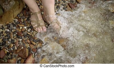Woman staying in water in shoes on a beach - Woman staying...