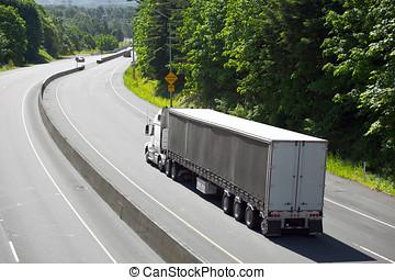 White semi truck long trailer on turn of highway