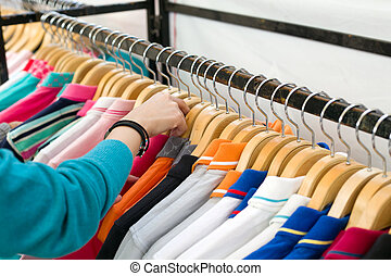 Young woman looking new shirt shopping in store.