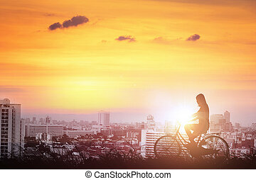 Silhouette of women bicycle valley in the city.