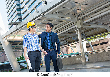 Young Male Architects Discussing with Businessman at...
