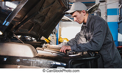 Mechanic male in automobile garage processing engine diagnostic - checking in hood of the car for luxury SUV