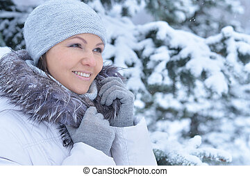 beautiful young woman posing outdoors in winter