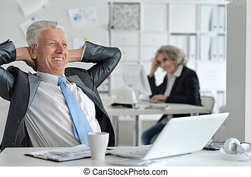 mature couple working at office, using computers