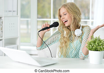 teen girl singing - Portrait of a teen girl singing into a...