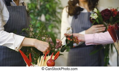 Three young handsome chef florists work at flowers fruit shop making fruit and vegetable bouquet