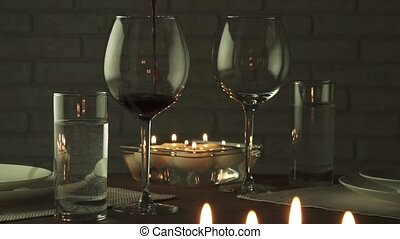 Glass filled with red wine at candlelight romantic evening...