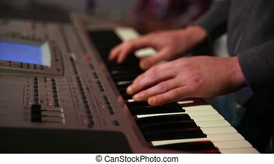 Young man playing electronic keyboard - Close up hands of...