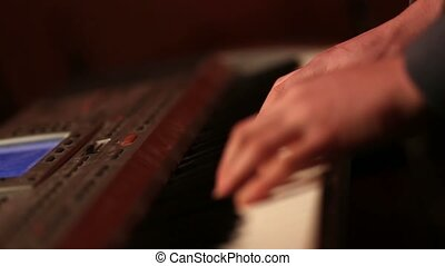 Human hands playing piano atthe party. - Close up of...