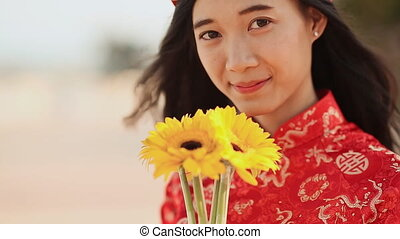 Beautiful Vietnamese girl in red traditional dress Ao Dai with yellow flowers. Close-up.