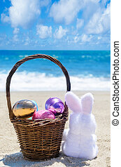Easter bunny with basket and color eggs on the ocean beach -...