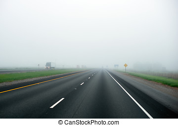 Foggy highway with dividing strip marking of green grass and...
